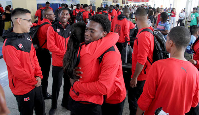 National hockey player Kristien Emmanuel, centre, brother of deceased Kwasi Emmanuel, is consoled by a female player at the Piarco International Airport yesterday.