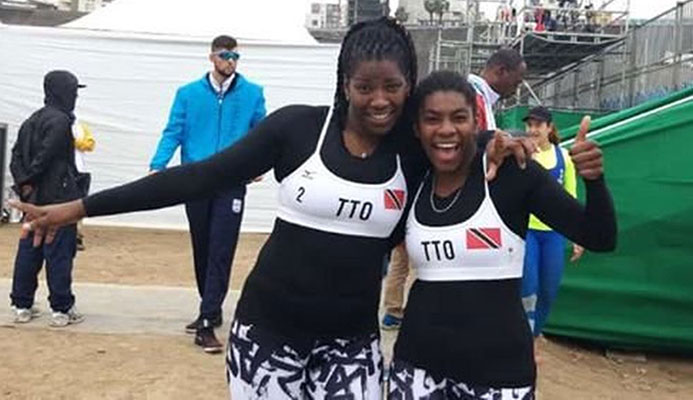 T&T beach volleyballers Rheeza Grant, left, and Malika Davidson are all smiles after defeating USVI, 2-0, yesterday at the Pan American Games in Lima, Peru.