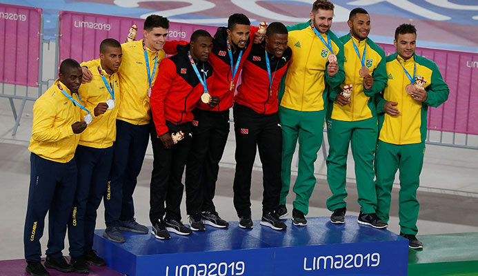 Colombia which won silver, left, T&T which won gold with Keron Bramble, Njisane Phillip and Nicholas Paul, and team Brazil which won bronze, pose for photos during the medal ceremony for the men's cycling track team sprint at the Pan American Games in Lima, Peru on Thursday. (AP)